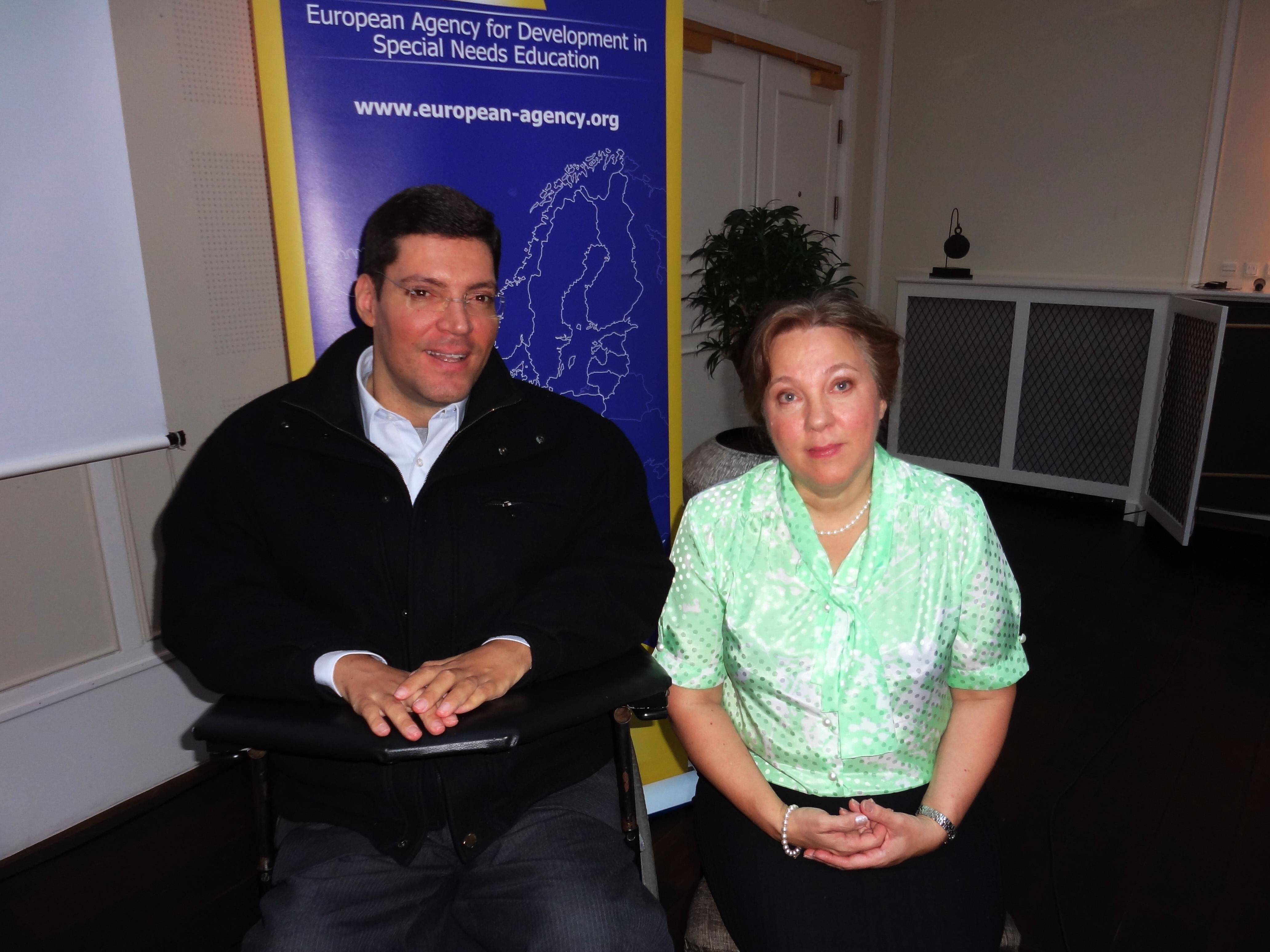 Em destaque, Rodrigo e uma mulher sentada posam lado a lado para a foto. Atrás deles, banner de fundo azul com mapa delineado em branco escrito em inglês 'European Agency for Developmente in Special Needs Education'.