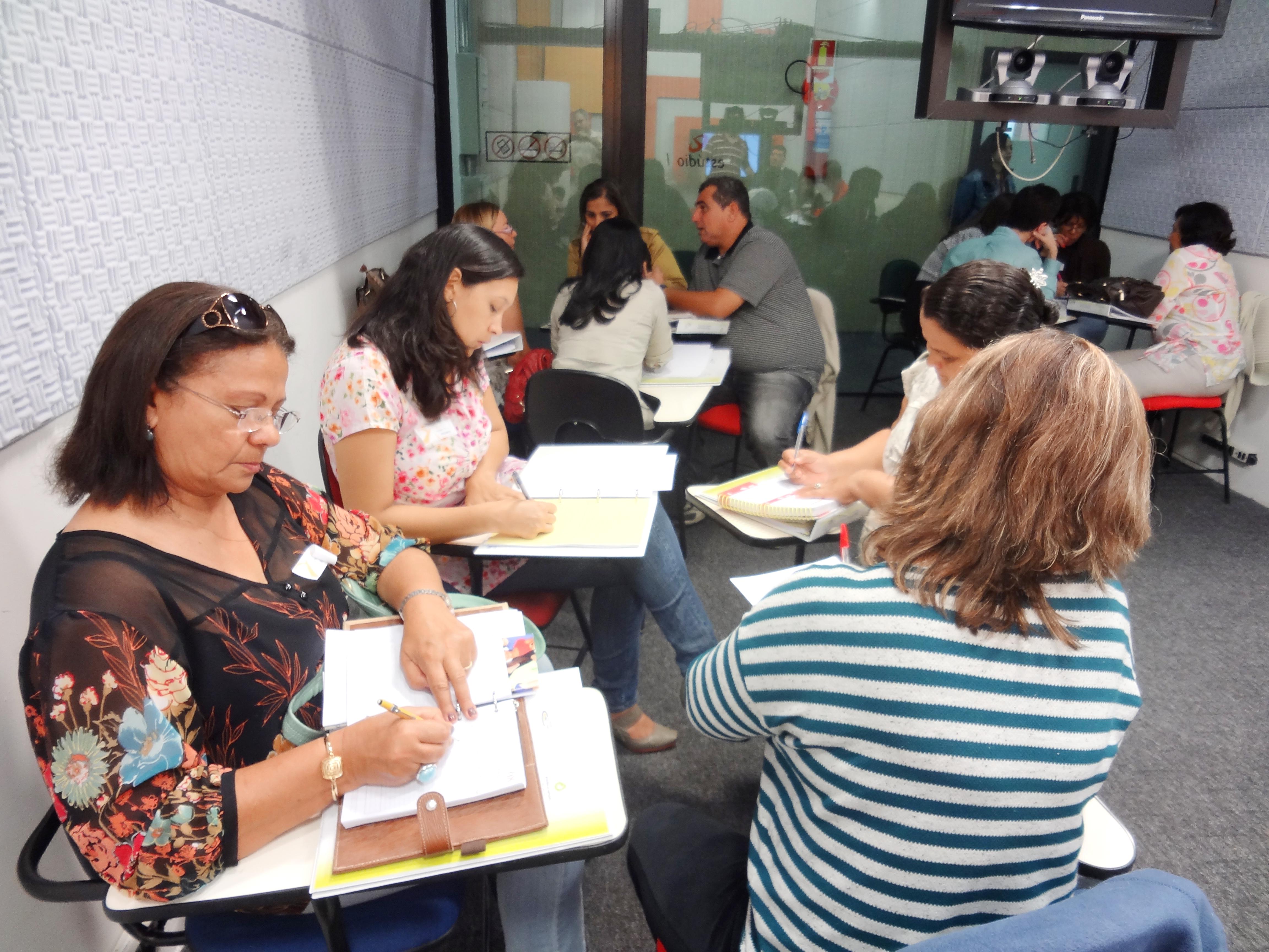 Divididos em quartetos dispostos pela sala, homens e mulheres fazem anotações em seus cadernos e conversam entre seus grupos. Eles estão sentados em cadeiras universitárias.