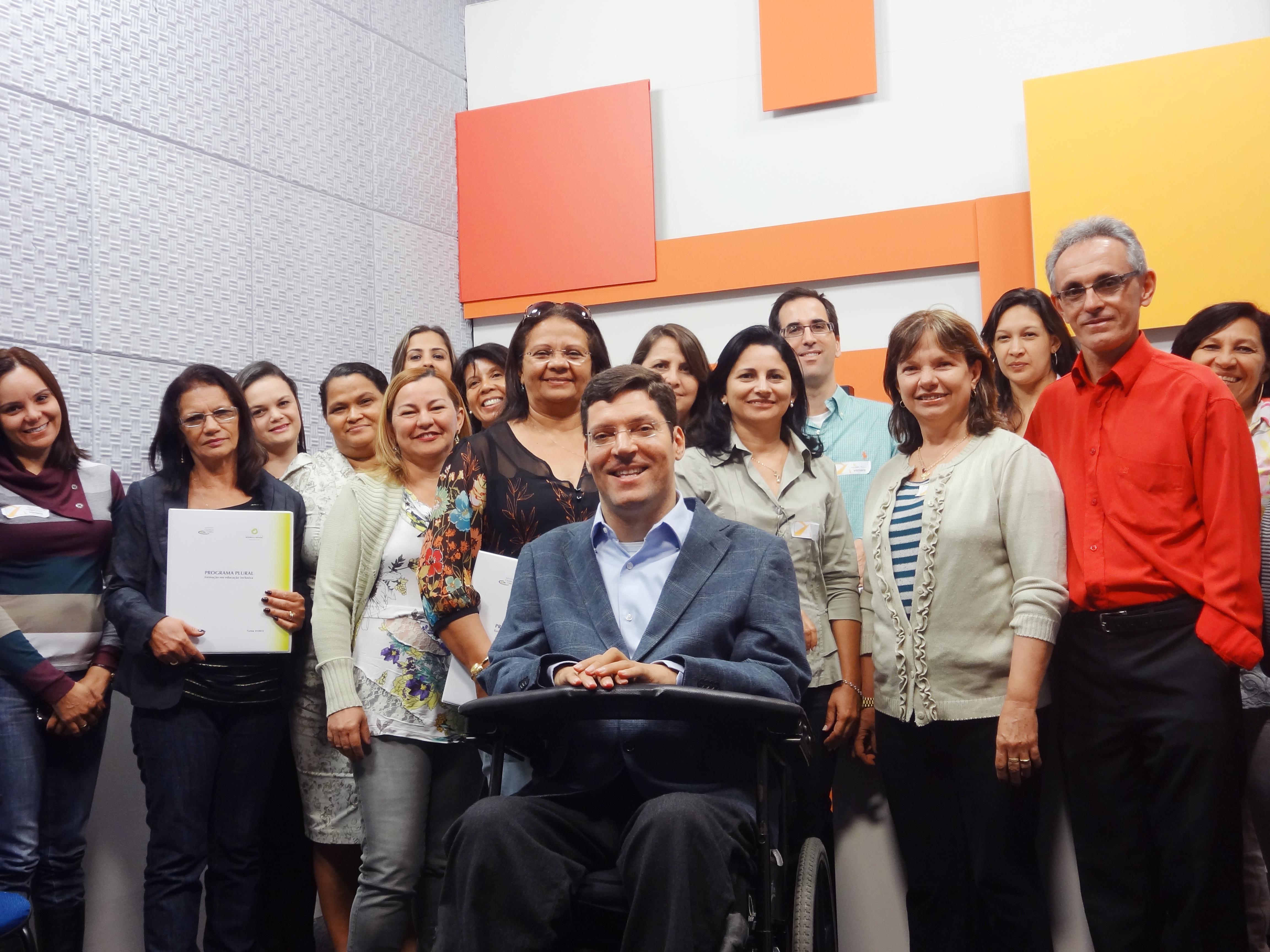 Mulheres e homens posam sorridentes e enfileirados para foto dentro de sala com paredes coloridas. À frente deles está Rodrigo em sua cadeira de rodas.