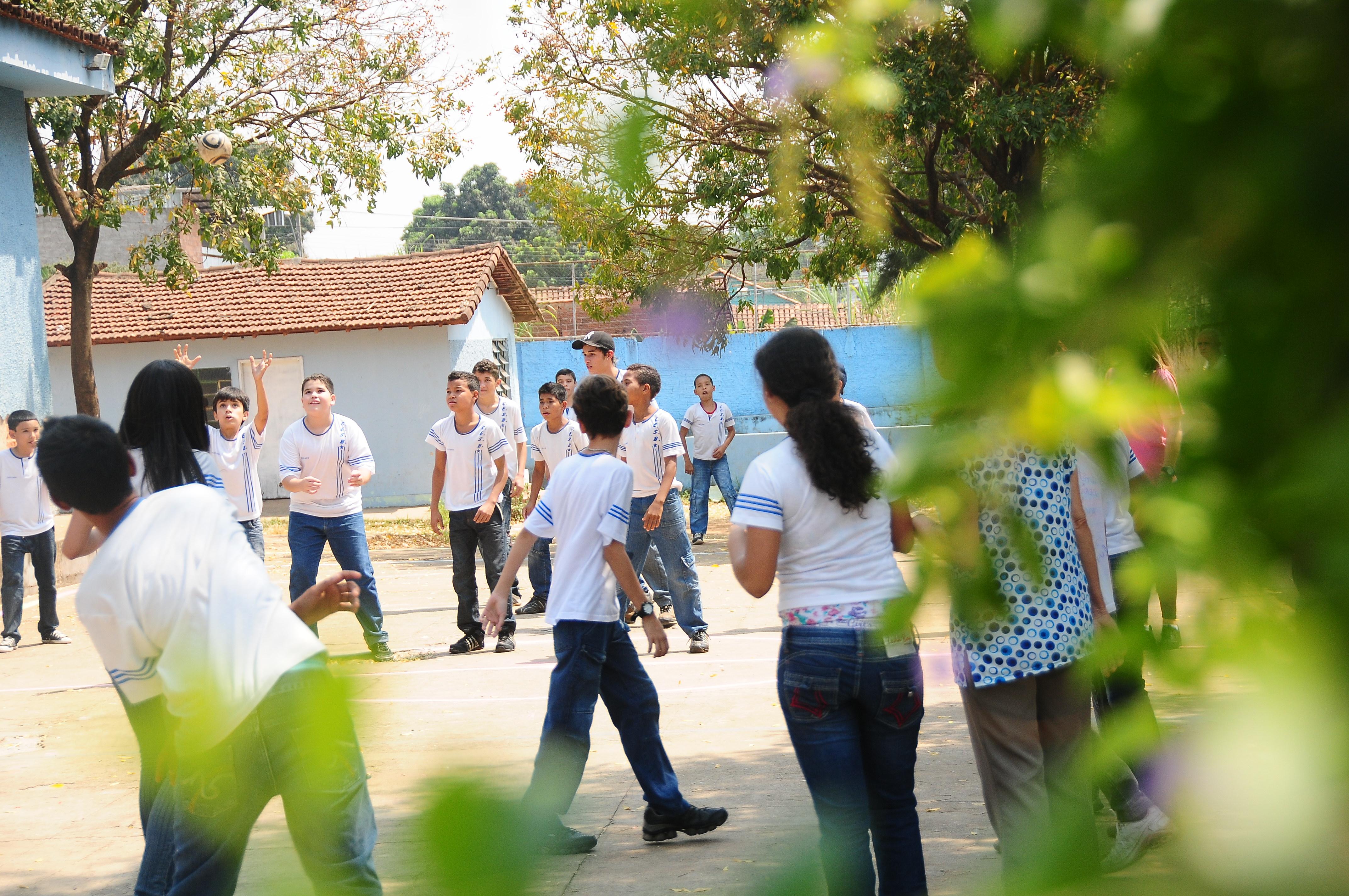 Garotos e garotas uniformizados brincam com bola em pátio do colégio em dia ensolarado.