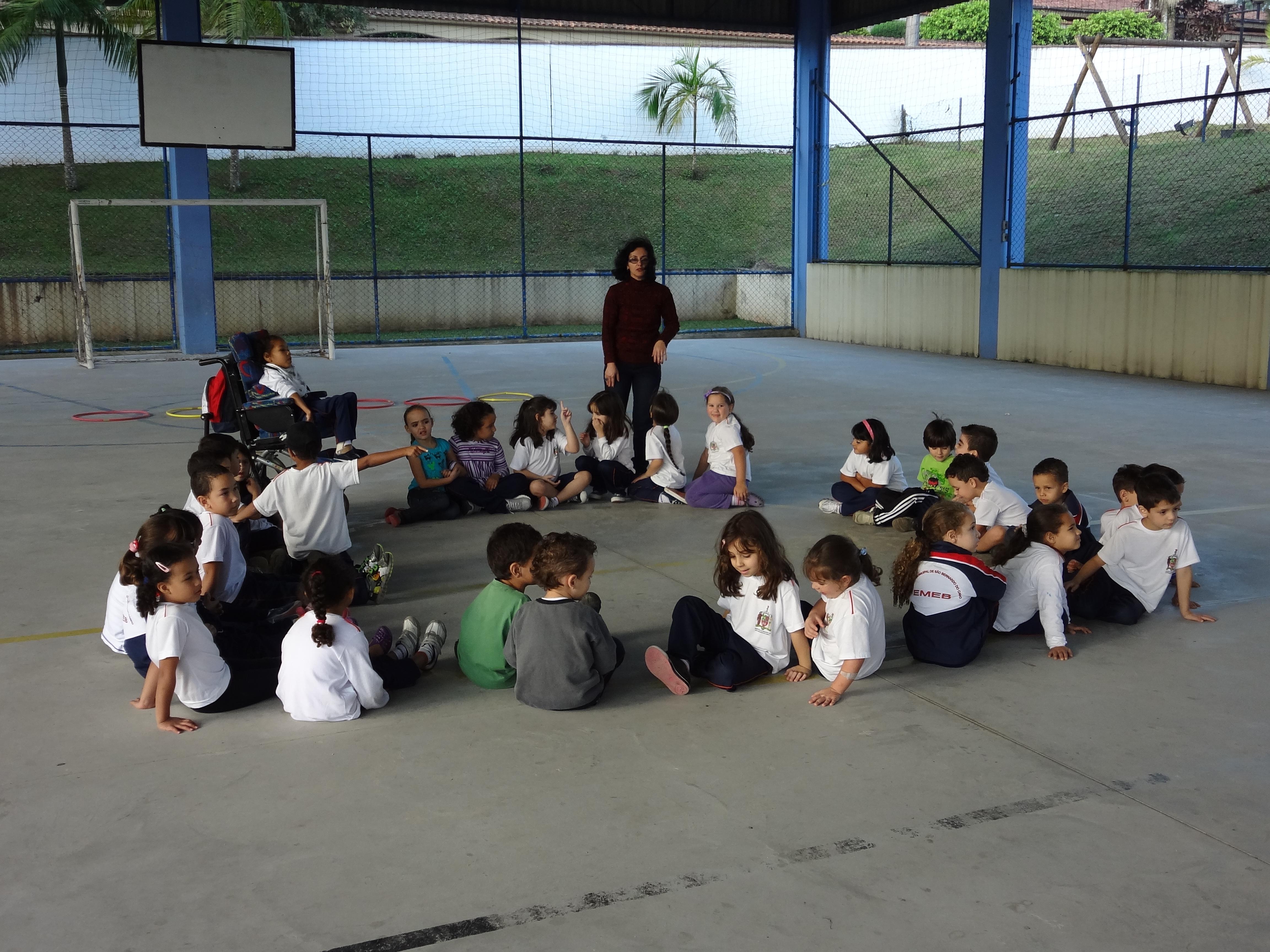 Crianças com e sem deficiência estão sentadas em roda e a professora está em pé, próxima ao grupo. Eles estão em uma quadra poliesportiva coberta e cercada por grades.