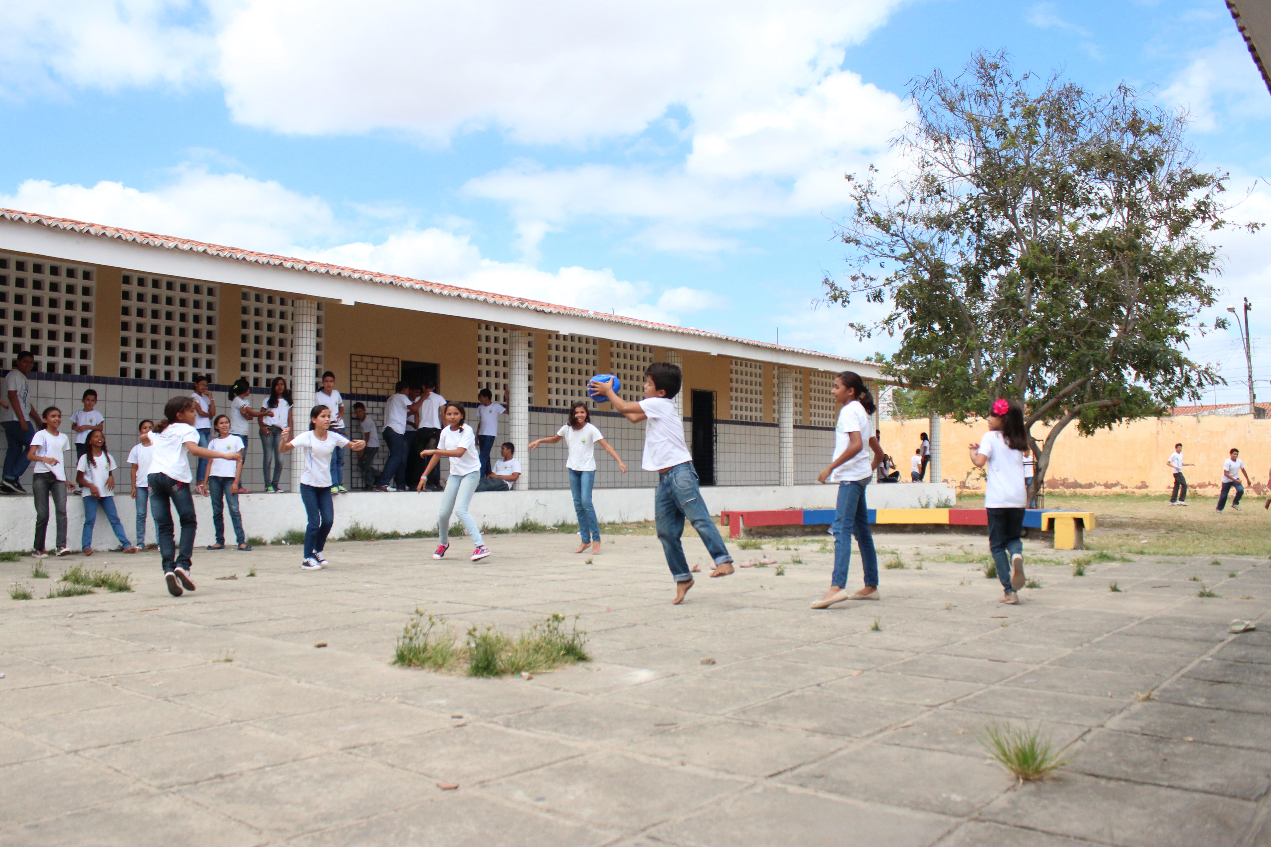 Crianças brincam em pátio a céu aberto de escola. Um dos garotos, descalço, segura a bola com uma das mãos e os demais se movimentam no espaço. Ao fundo, outro grupo observa o jogo apoiado na mureta do prédio escolar.