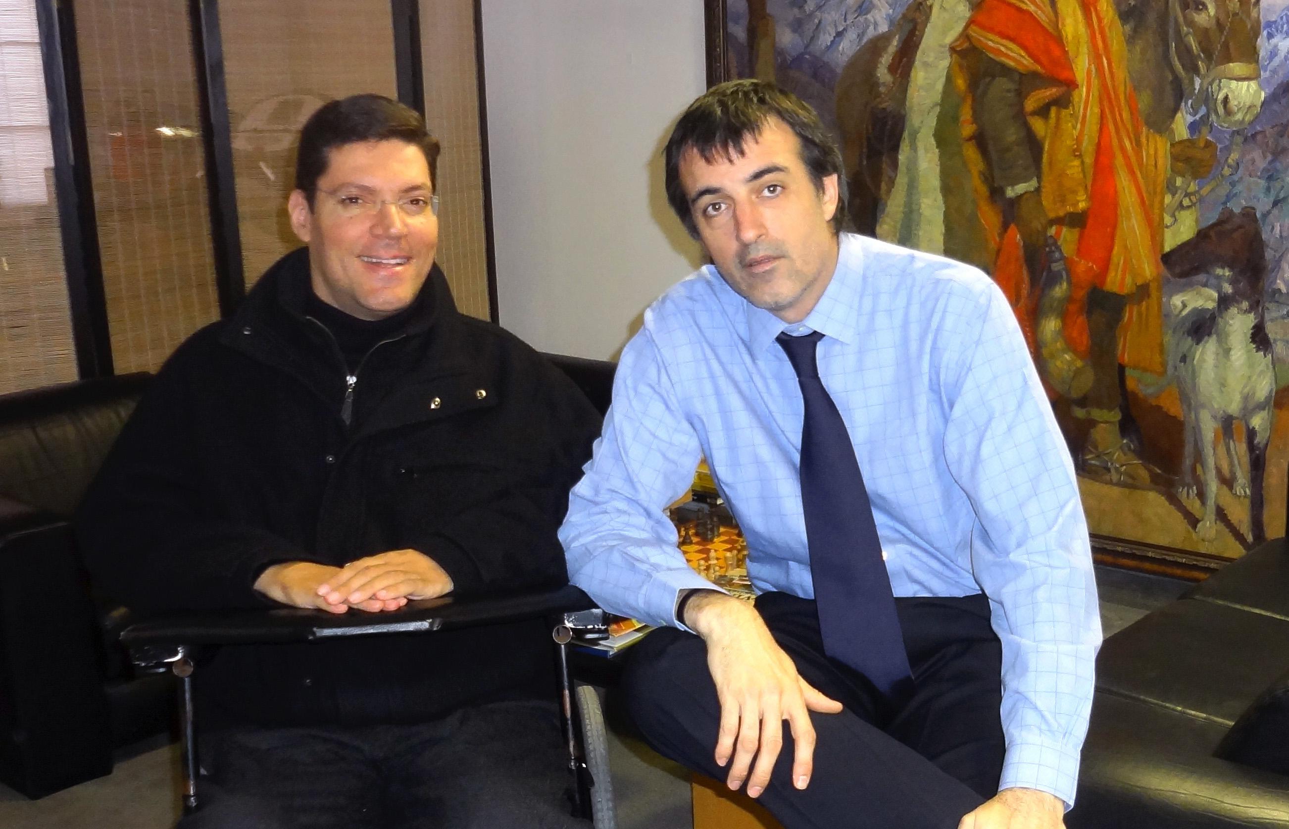 Rodrigo sorri para foto ao lado de homem vestido em traje social. Eles estão em um escritório e posicionados a frente de um quadro abstrato e colorido.