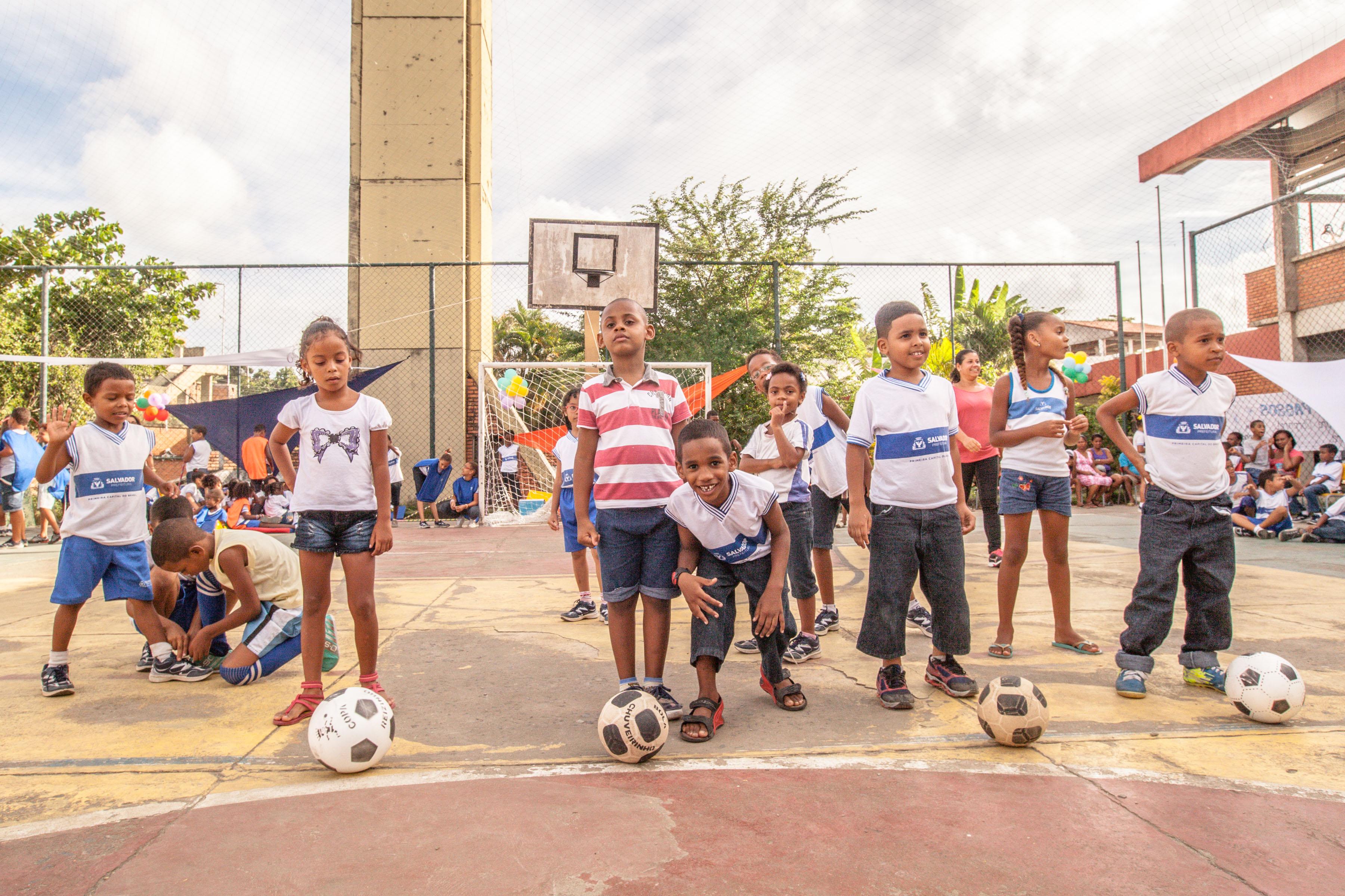 Em uma quadra poliesportiva meninos e meninas sorriem com bolas de futebol nos pés. Está um dia ensolarado e há árvores no fundo da quadra.