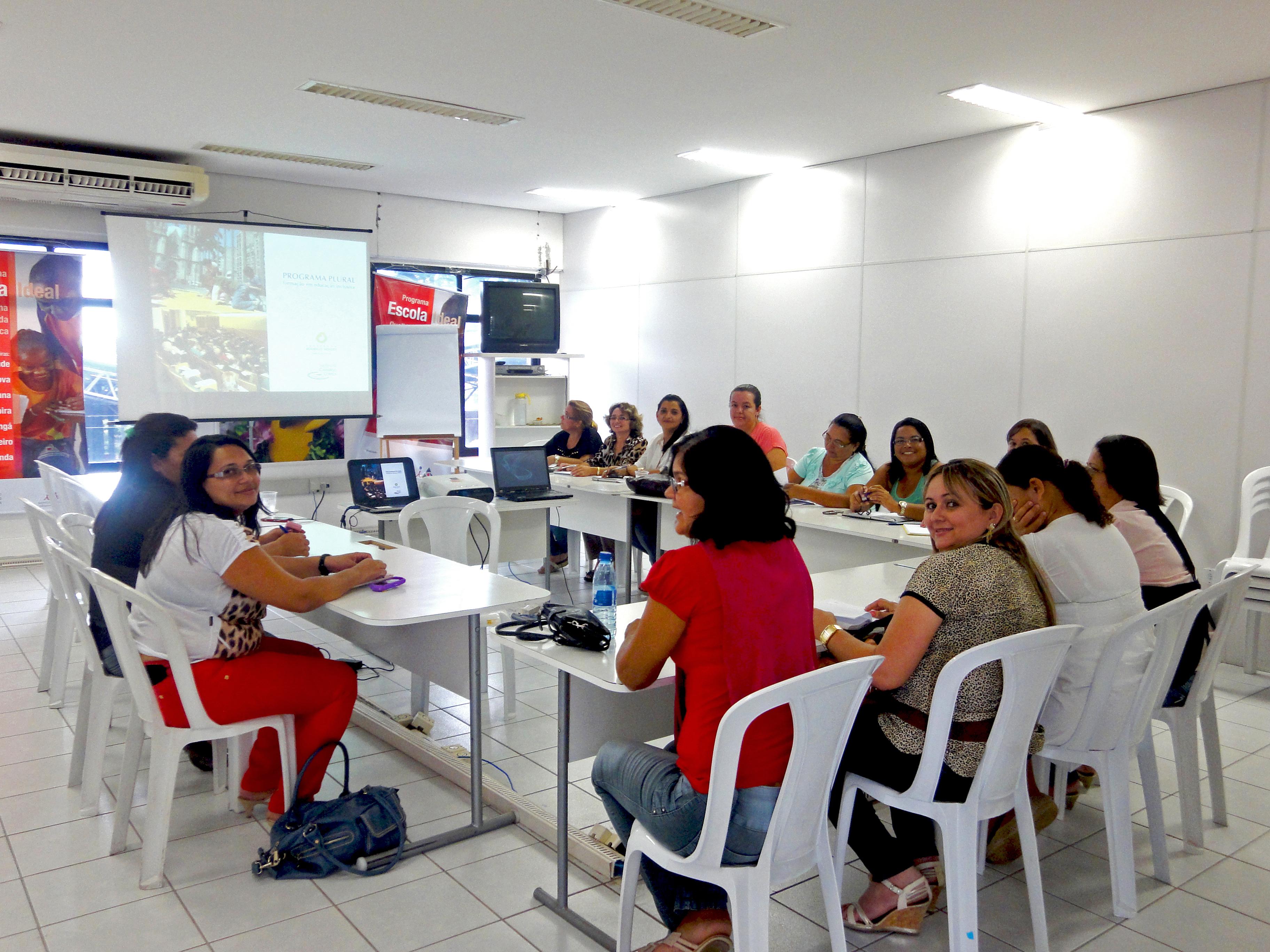 Em sala branca e iluminada, grupo de mulheres sentadas em mesas dispostas em formato U posam para a foto. Ao fundo, há um projetor e telão.
