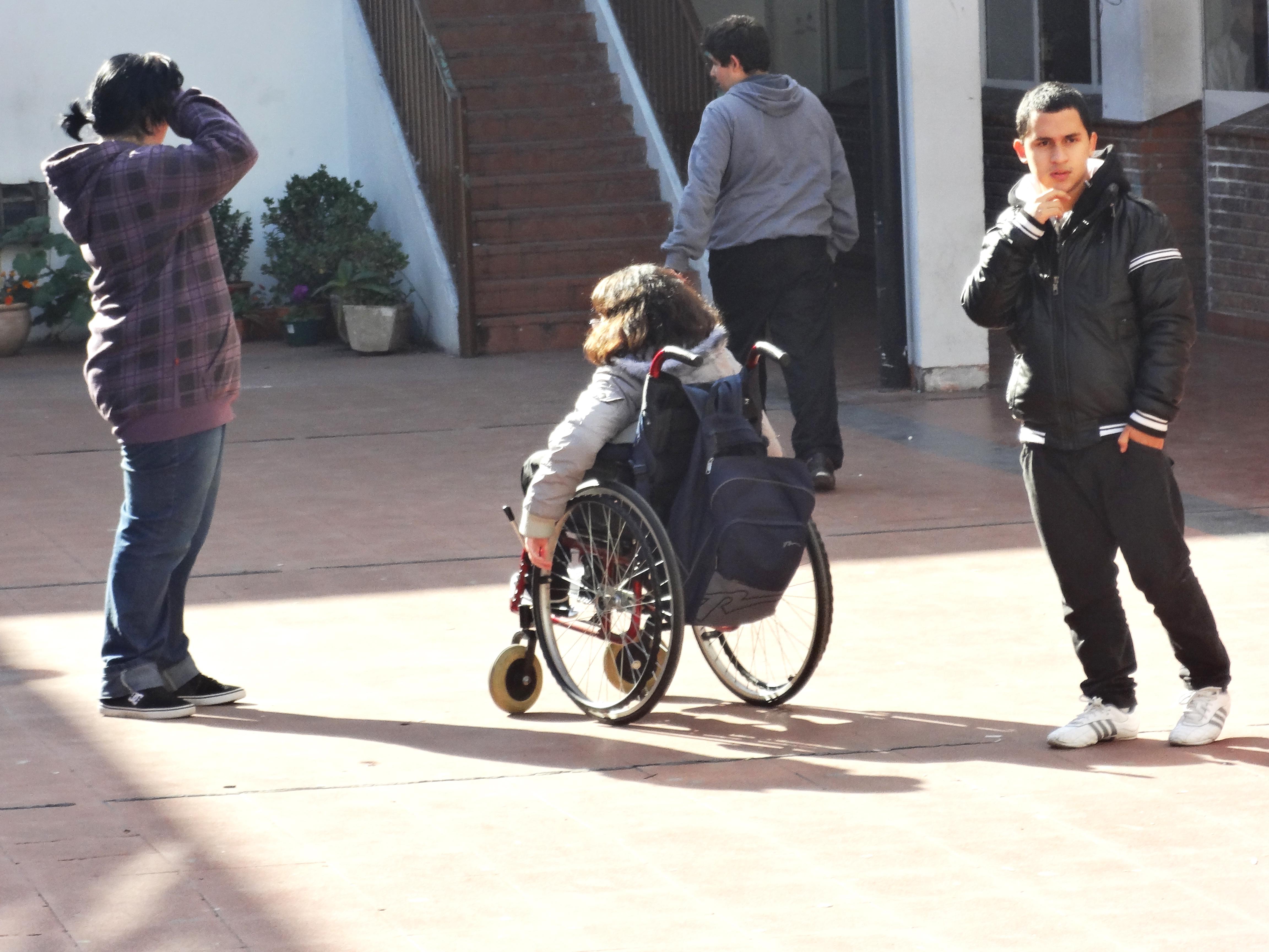 Menina em cadeira de rodas se movimenta entre outros jovens sem deficiência no pátio da escola.
