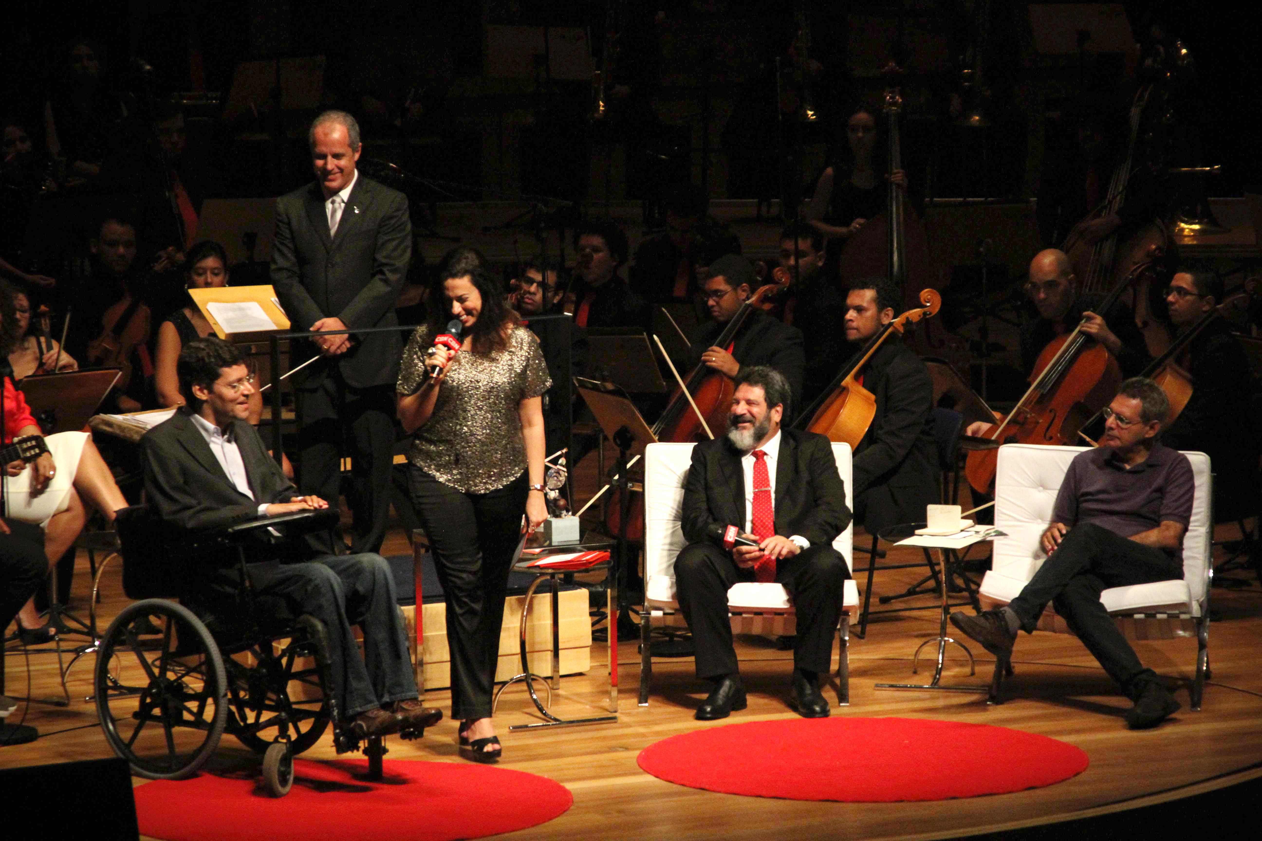 Em um palco, Rodrigo em sua cadeira de rodas, está ao lado de mulher que segura microfone. Ao lado direito da imagem, dois homens sentados em poltronas. Ao fundo maestro e orquestra. Todos sorriem e olham para Rodrigo.