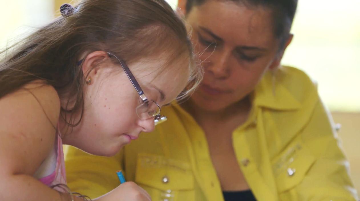Garota com síndrome de Down está concentrada em suas anotações. Ela está de perfil e ao seu lado, a professora a observa.