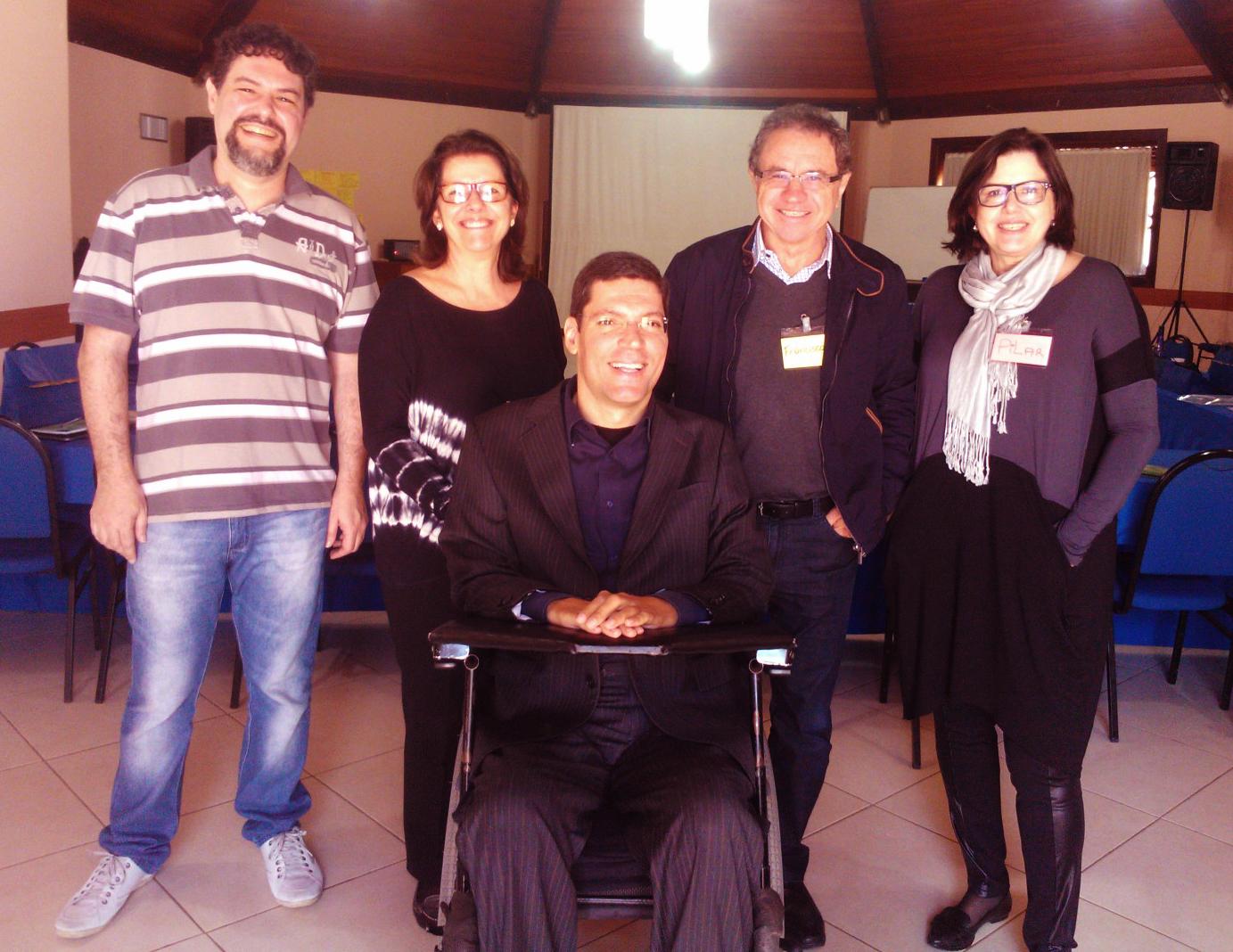 Cinco pessoas posam sorridentes para fotografia em auditório. Eles estão em pé e Rodrigo ao centro em cadeira de rodas.