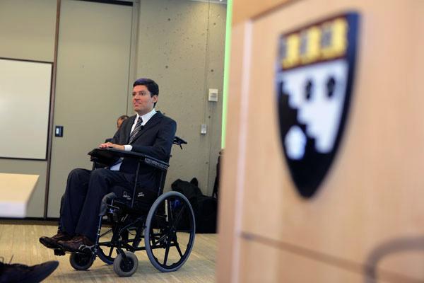 Porta entreaberta com brasão de Harvard. Dentro da sala, Rodrigo está em sua cadeira de rodas.