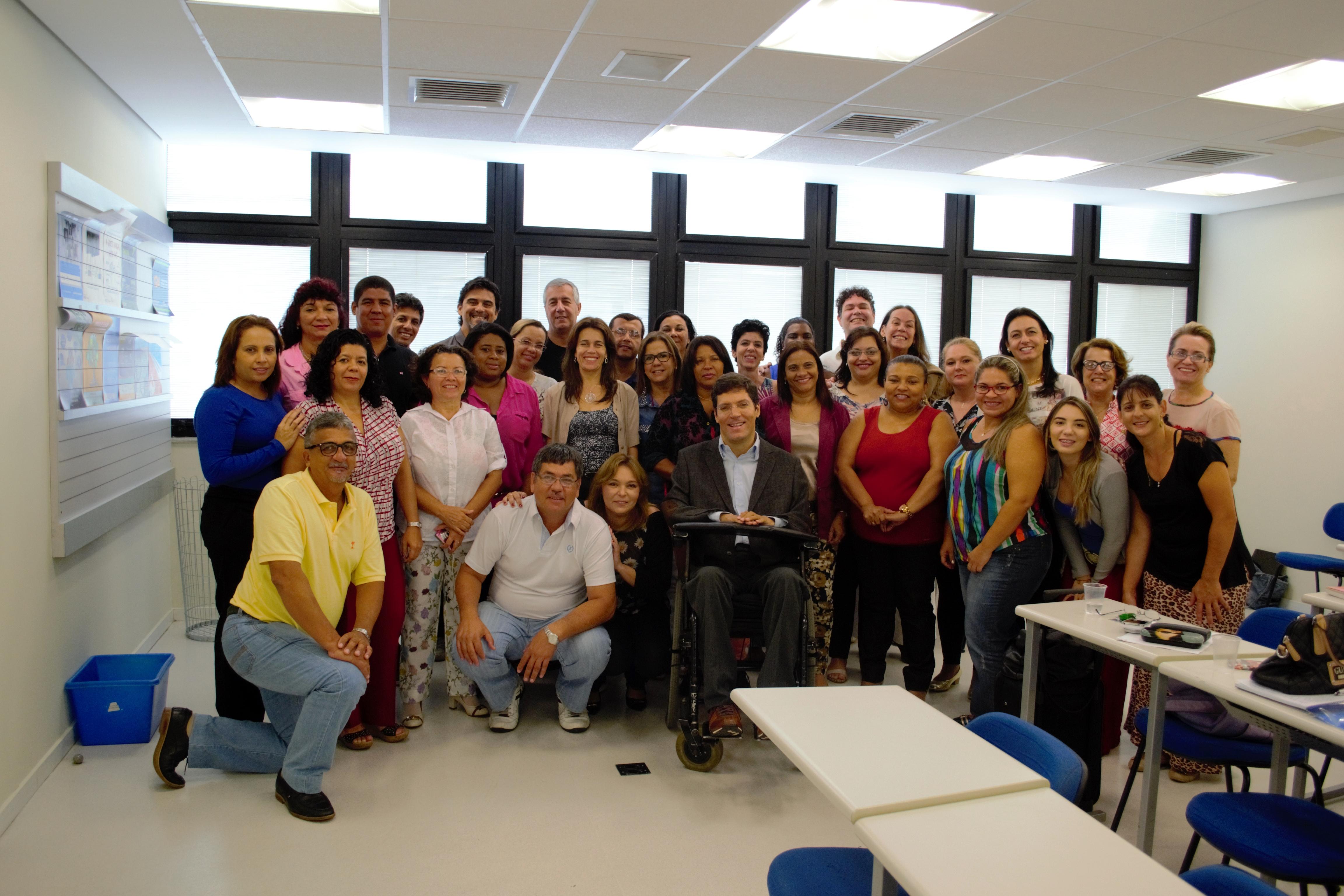 Homens e mulheres posam para a foto agrupados próximos ao Rodrigo, que está no centro do grupo, em cadeira de rodas. Ao fundo, as janelas da sala de aula.