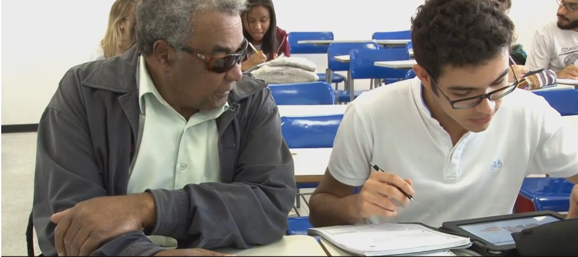 Homem idoso com deficiência visual presta atenção em jovem sentado ao lado direito, que manuseia caderno e tablet. Eles estão em uma sala de aula, sentados lado a lado em mesas escolares.