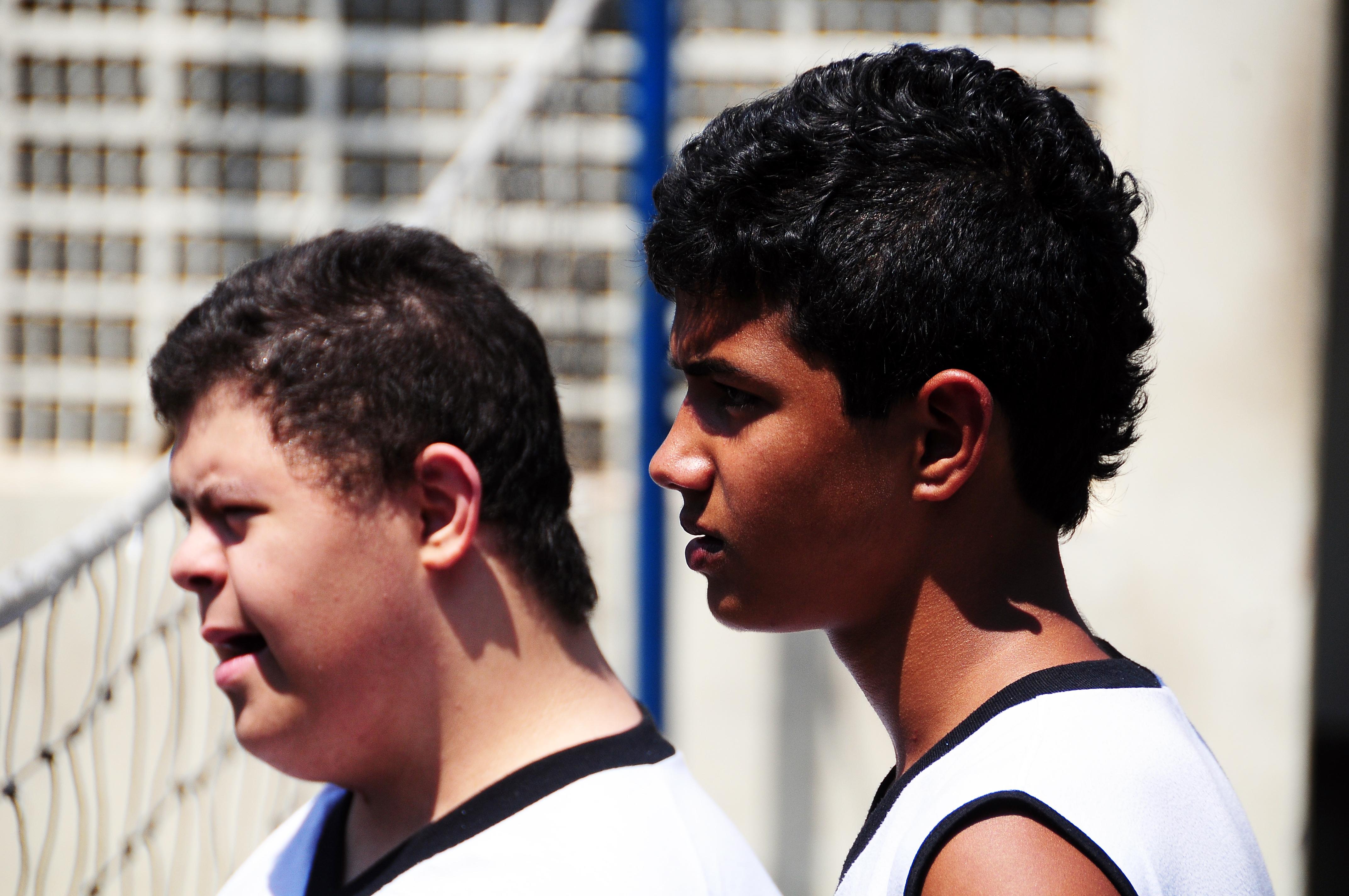Garoto com síndrome de Down e garoto sem deficiência estão lado a lado e de perfil olhando atentamente através de rede.