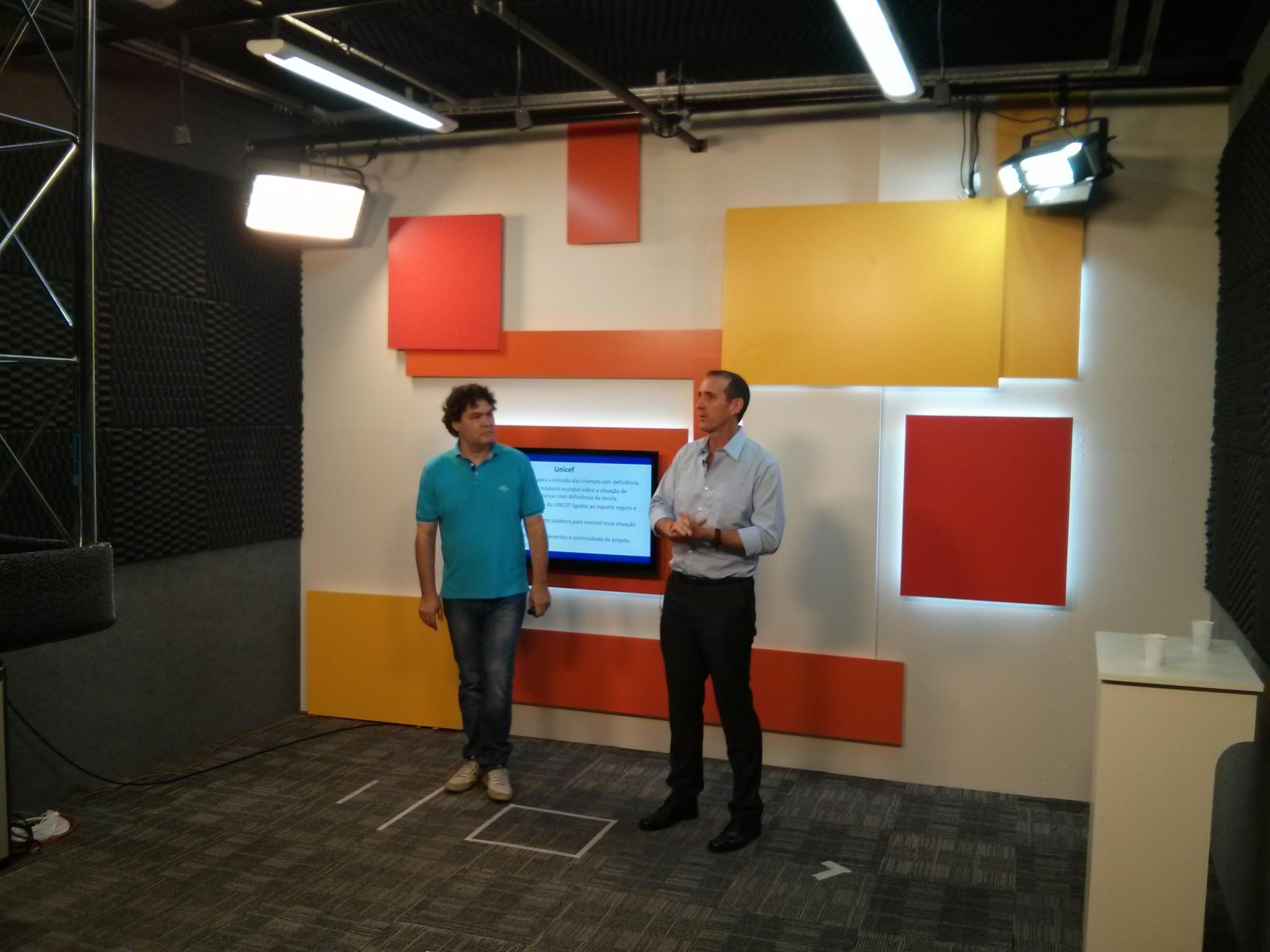 Em estúdio, dois homens estão em pé, a frente de uma parede com quadrados coloridos. Na parede há uma televisão e dois refletores posicionados nos cantos superiores.