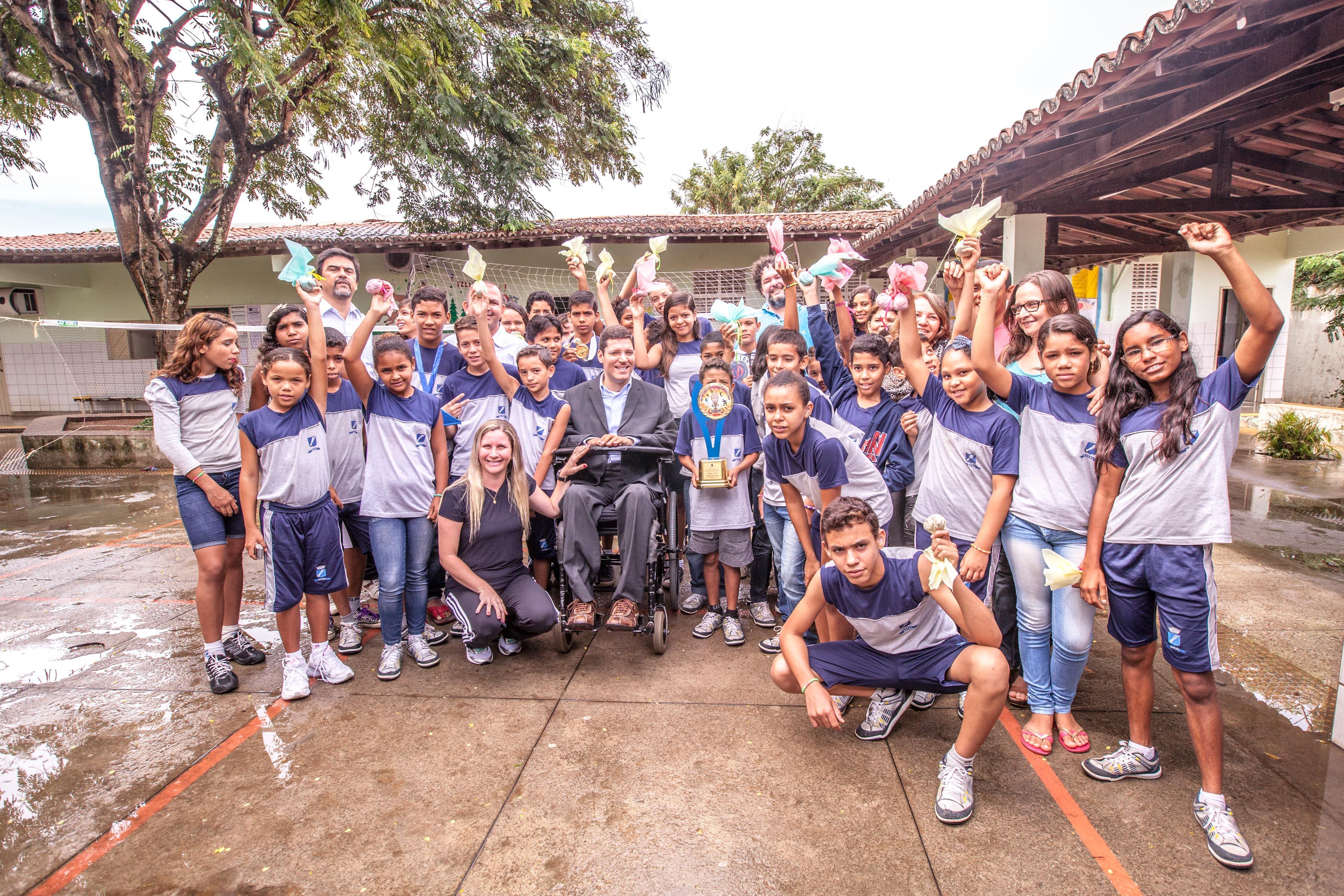 Crianças uniformizadas e educadores posam para foto junto a Rodrigo em pátio de escola. Todos estão sorridentes e alguns estão com os braços erguidos segurando petecas.