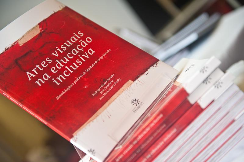 """Livro posicionado de pé em suporte sobre pilha de livros. Em destaque, o título """"Artes visuais na educação inclusiva – metodologias e práticas do Instituto Rodrigo Mendes"""", em fundo vermelho. A bordas superior e inferior da capa são brancas e na parte inferior há o logotipo da Editora Petrópolis."""