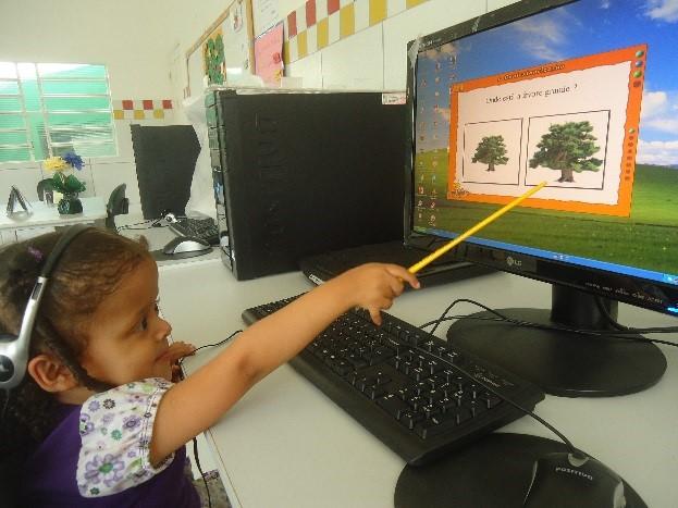 Menina sentada a frente de computador aponta com vareta para a tela onde há figuras de duas árvores, sendo uma maior que outra. Ela está concentrada na atividade e usa fones de ouvido.