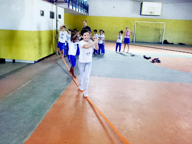 Em quadra poliesportiva, três crianças caminham sobre fita laranja esticada enquanto seguram-se em corda na altura de seus ombros. Ao fundo, outras crianças aguardam em fila junto ao professor.