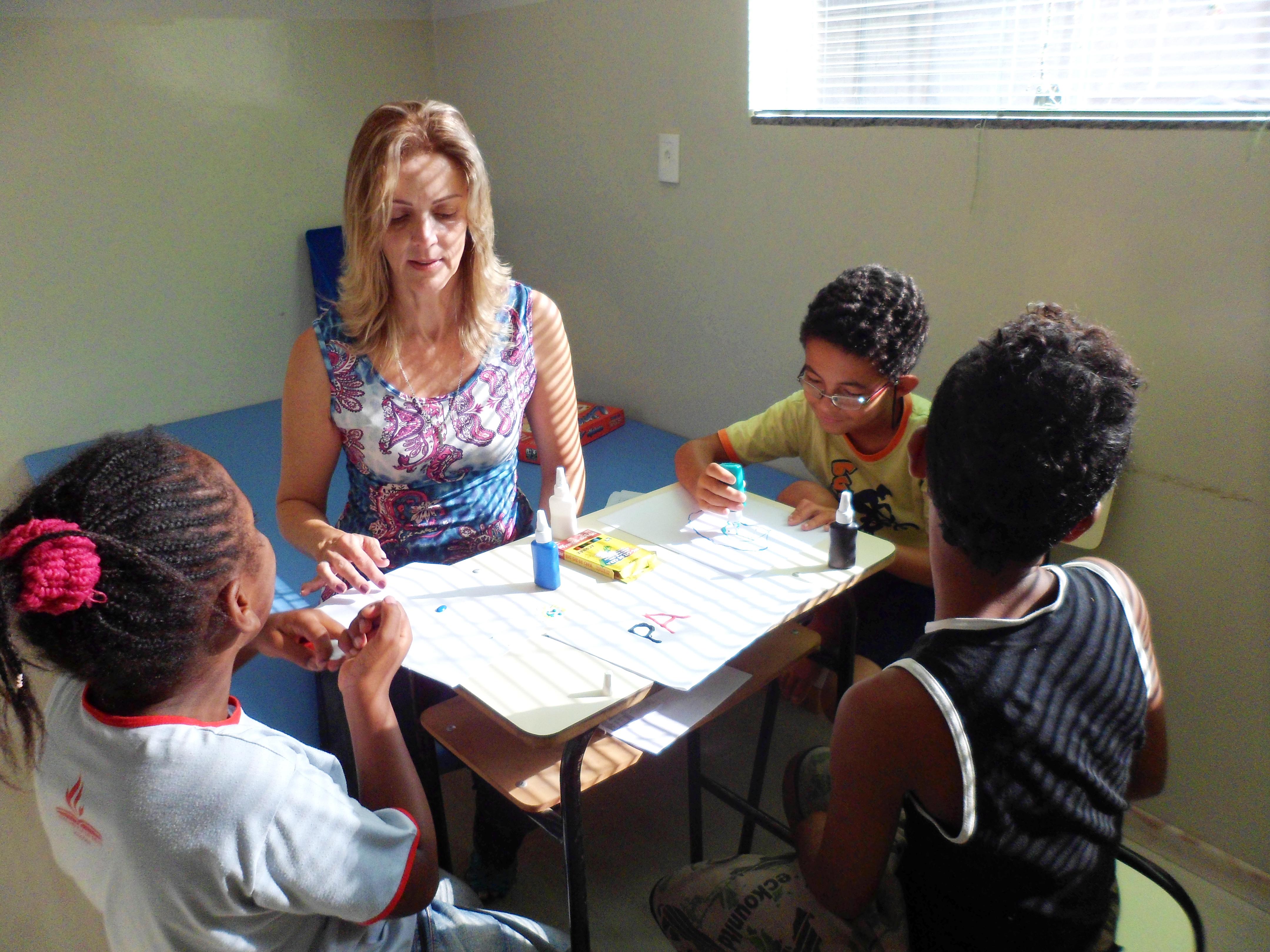 Em mesa escolar, estão sentadas três crianças e uma professora. Duas interagem com a professora, enquanto a terceira pinta com tinta-cola em folha branca.