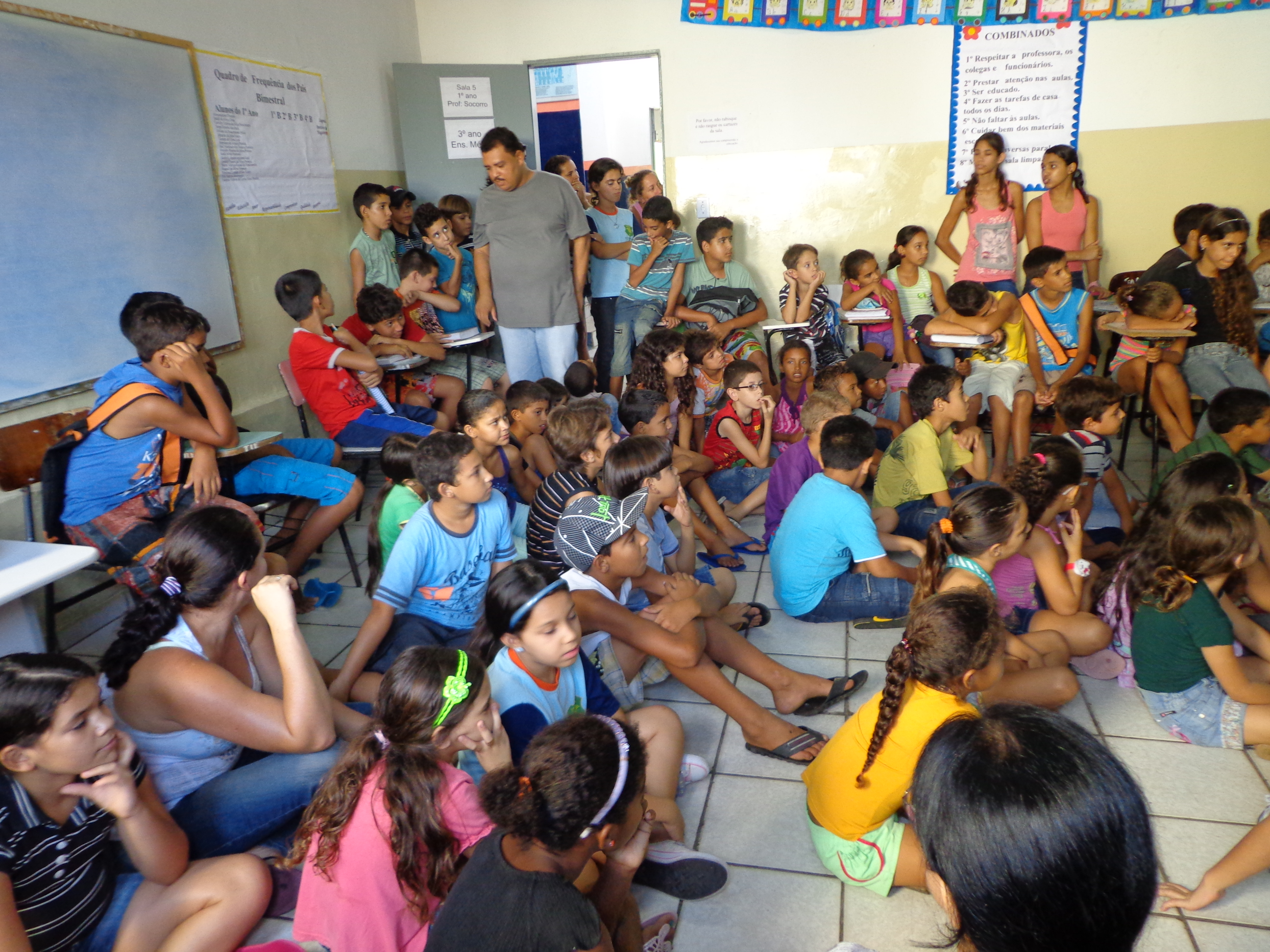 Crianças e adolescentes sentados no chão e cadeiras encostadas na parede da sala de aula. Eles estão voltados para a lousa.