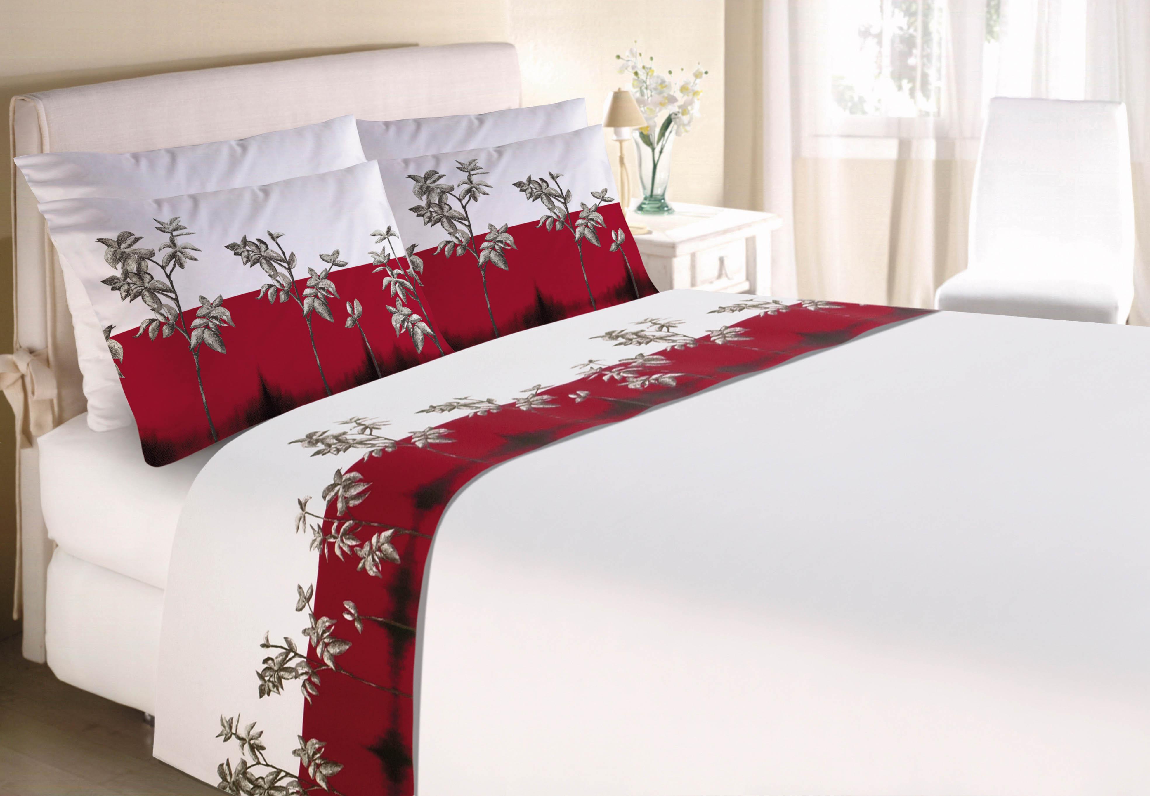 Em destaque cama de casal com jogo de lençóis e fronhas brancos com obra de arte com galhos folheados em fundo vermelho. Ao fundo, quarto mobiliado em branco.