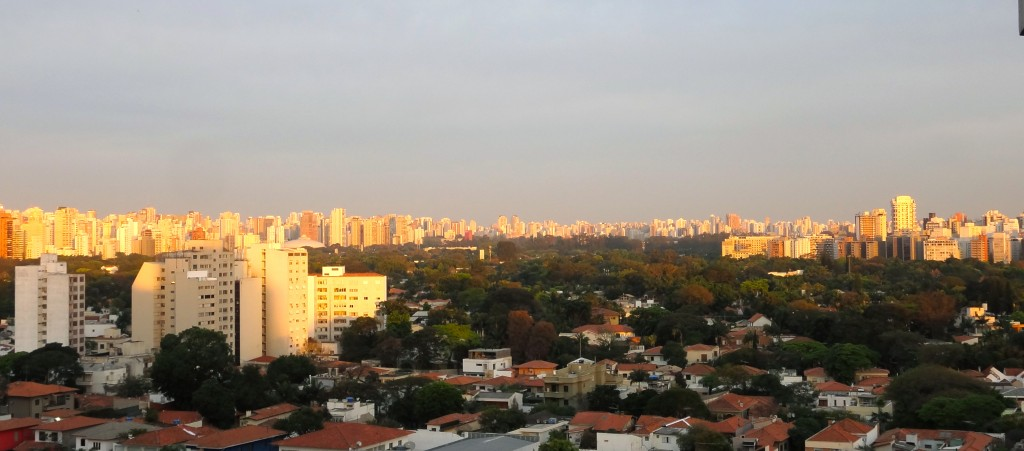Imagem panorâmica de uma cidade, há muitos prédios ao horizonte e uma grande região arborizada ao centro. É um fim de tarde e a luz do sol confere uma cor alaranjada às edificações.