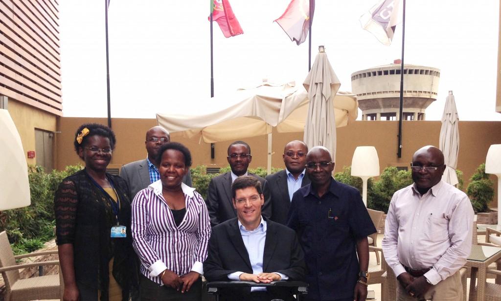 """alt=""""Em ambiente aberto, mulheres e homens vestidos em traje social posam para foto em pé. Rodrigo está sorridente e ao centro da imagem. Ao fundo, estão hasteadas as bandeiras de Angola e Luanda."""