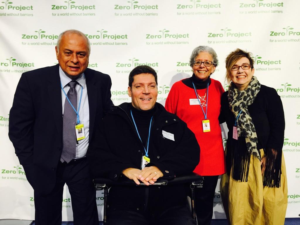 Rodrigo Mendes sorri para fotografia ao lado de outras quatro pessoas diante de um painel com logos da Conferência Zero Project