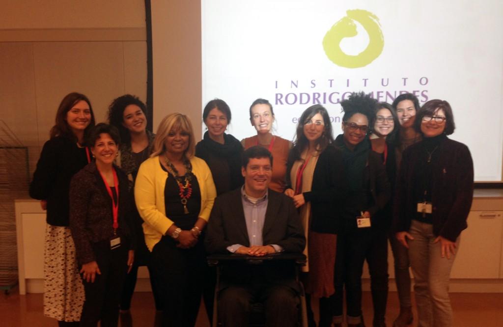 Pessoas posam sorridentes para foto. Na parede ao fundo, logo do Instituto Rodrigo Mendes é projetado.