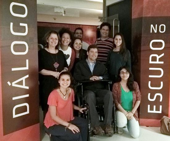 """Seis mulheres e três homens estão em grupo diante da porta de entrada da mostra """"Diálogo no Escuro"""""""