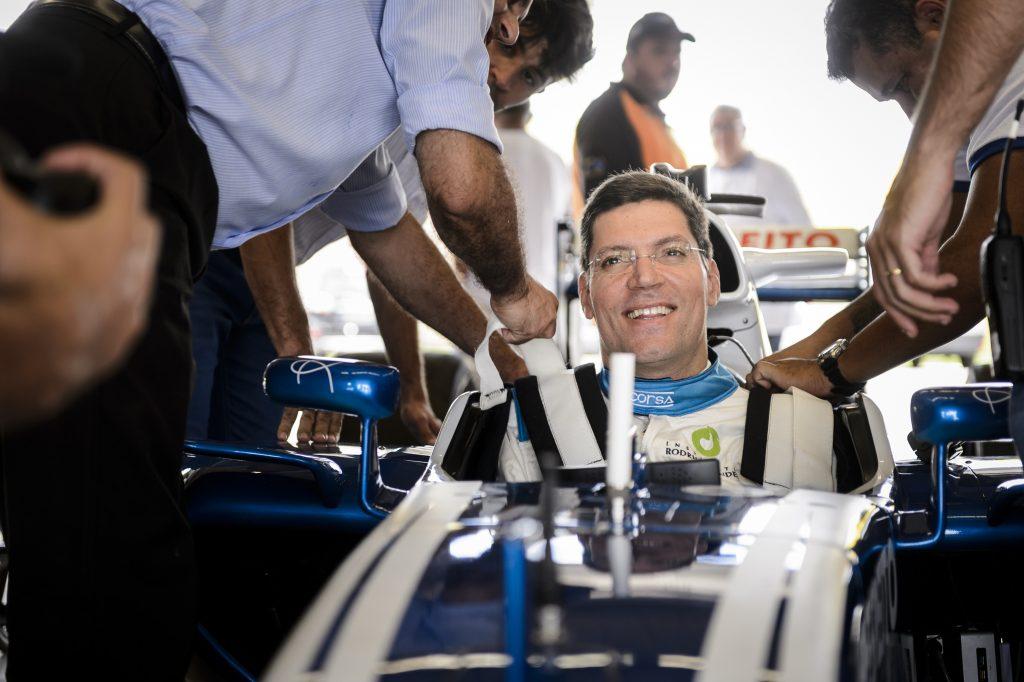 Rodrigo Hübner Mendes em um carro de formula 1, muitas pessoas em sua volta