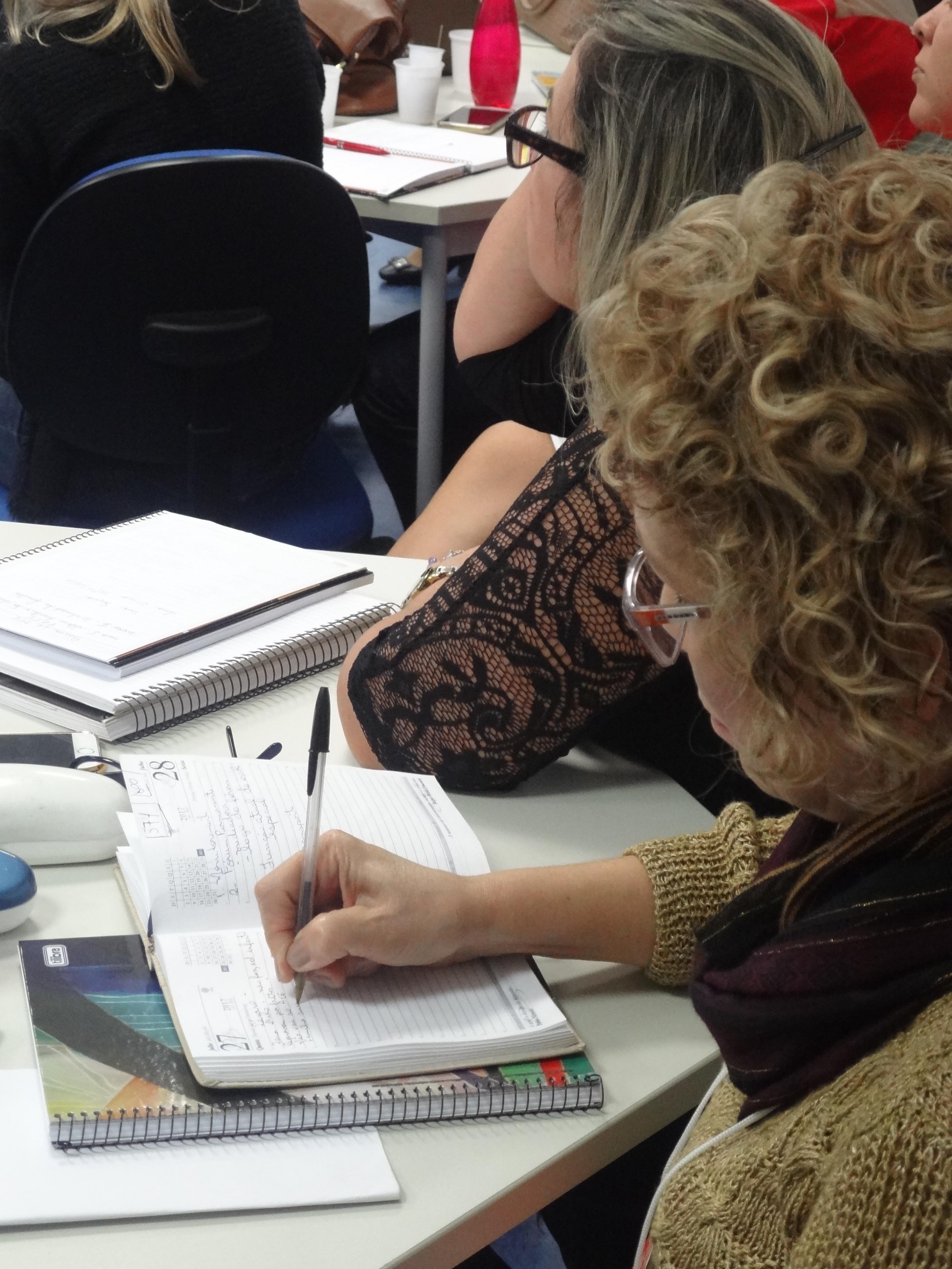 Mulher de perfil escreve em agenda