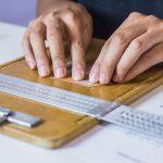 Mãos de mulher colando legendas em braille em cima de uma prancheta com o reglete (instrumento usado para criação do braille).
