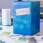 Lata de tinta pintada de azul com adesivo escrito Lata de criação de histórias, sobre mesa branca com outras imagens em cima da mesma.