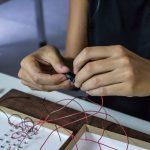 Mãos de mulher conecta fios vermelhos para formar um circuito eletrônico.