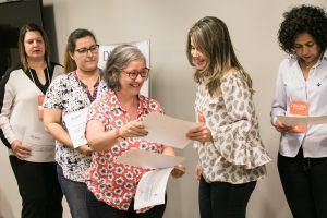 No centro da imagem, uma mulher sorridente entrega um certificado a uma das participantes do DIVERSA Presencial 2017. Ao lado delas, outras mulheres seguram seus certificados.