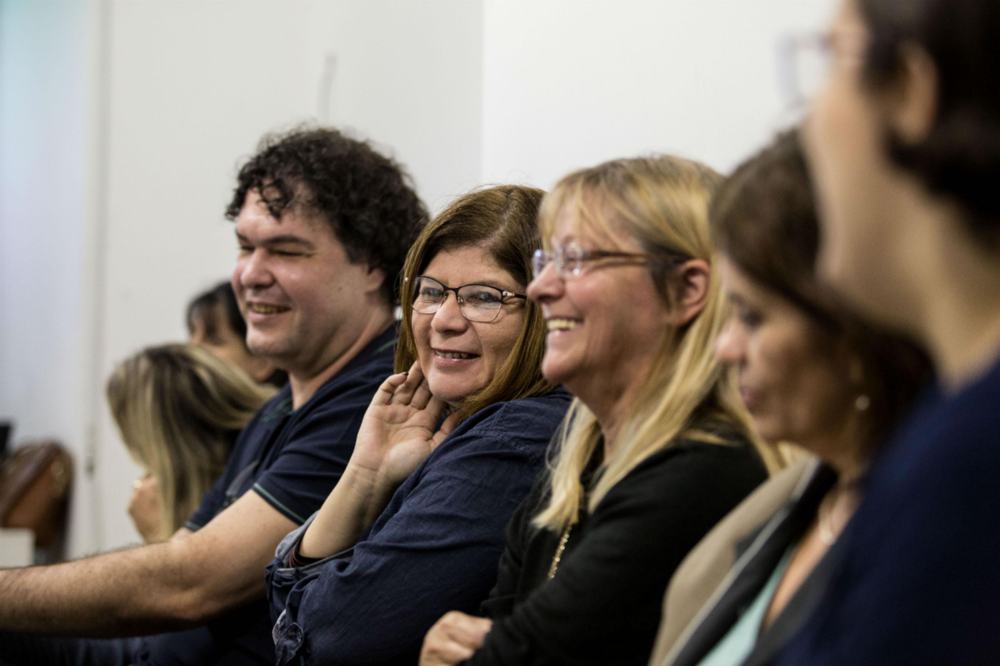 Pessoas sentadas, lado a lado, em uma sala sorriem.