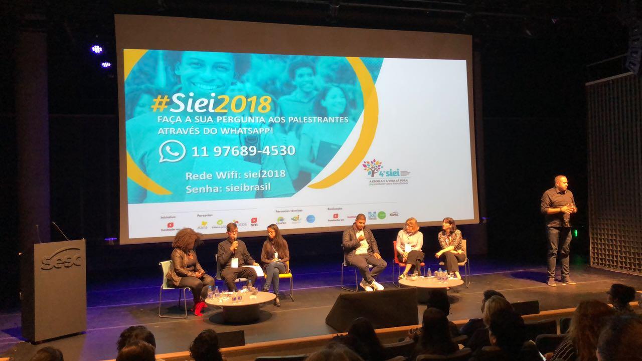 Palestrantes debatem sobre educação no seminário. No fundo do palco, uma projeção com a arte do seminário.