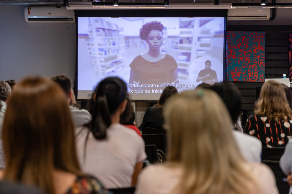 Grupo de pessoas assiste a um vídeo do curso em um telão.