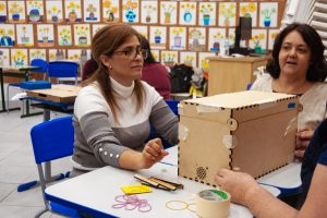 Três professores estão sentadas em um grupo de carteiras escolares. Sobre as mesas, há uma caixa de madeira e diversas ferramentas.