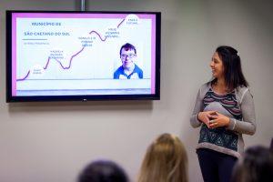 Uma professora mostra um slide com informações de um aluno com Síndrome de Down.