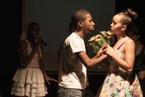 Trecho do musical em que um jovem entrega um buquê de flores para uma garota. Atrás, é possível ver alunos cantando.