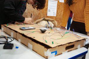 Uma professora usa uma ferramenta em uma estrutura feita de madeira com um circuito elétrico.