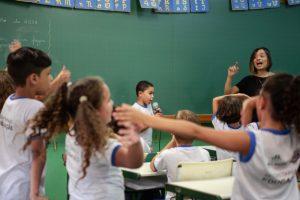 Em uma sala de aula, crianças dançam e cantam junto com professora.