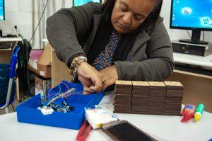 Mulher conecta dois fios de um dos materiais pedagógicos.