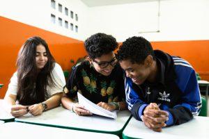 Os mesmos três estudantes apontam e sorriem olhando para uma folha de papel com braille.