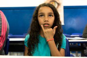 Menina de cerca de dez anos faz gesto em Libras.