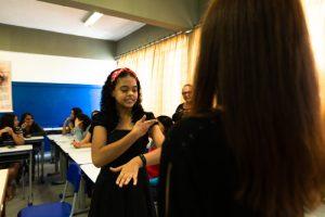 Duas adolescentes sinalizam em Libras em sala de aula.