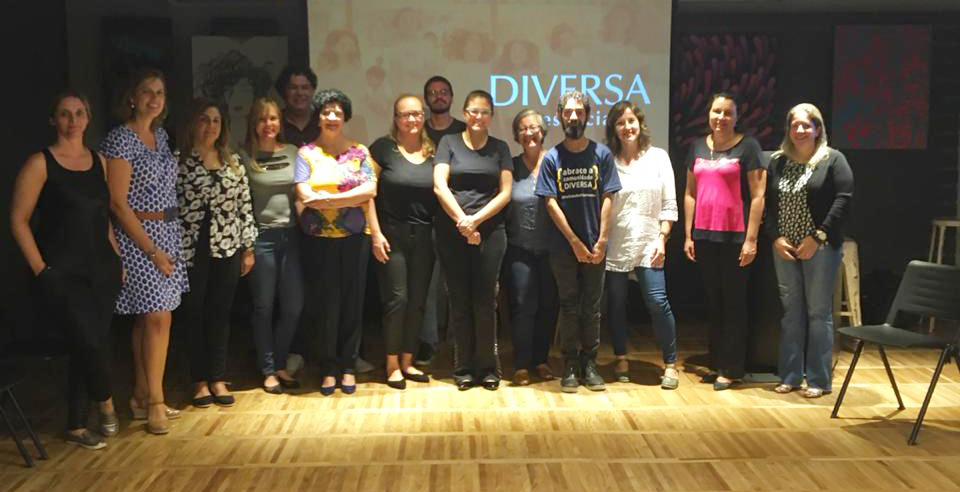 Grupo de educadoras e equipe do IRM posa para foto em frente de uma tela com o texto: DIVERSA presencial