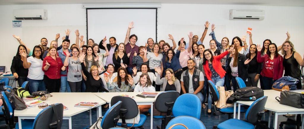 Diversas pessoas em sala de aula, posam com braços levantados.